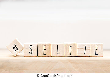 Wooden cubes with a Hashtag and the word selfie background, Social media concept