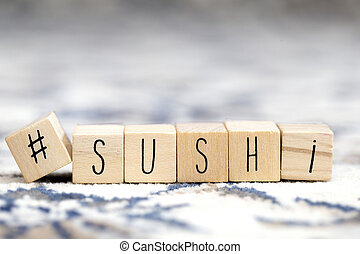Wooden cubes with a hashtag and the word Sushi, social media and food concept