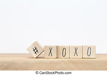 Wooden cubes with hashtag and XOXO hugs and kisses letters of love near white background, social media concept