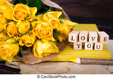 Wooden cubes with inscription LOVE YOU and bouquet of yellow flowers on vintage paper, wooden background. Selective focus