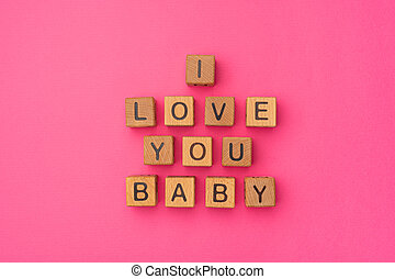 Wooden cubes with the phrase I Love You Baby on an empty colorful pink background. Words of love are made of letters from wood for your girlfriend, boyfriend, wife, husband, for Valentine's Day greeting romantic postcard
