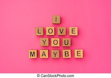 Wooden cubes with the phrase I Love You Maybe on an empty colorful pink background. Words of love are made of letters from wood for your girlfriend, boyfriend, wife, husband, for Valentine's Day greeting romantic postcard