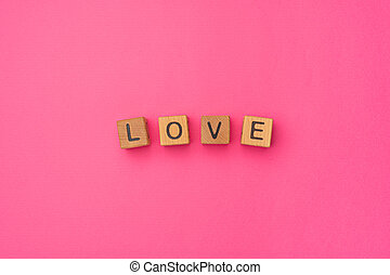 Wooden cubes with the word Love on an empty colorful pink background. Word of love are made of letters from wood for your girlfriend, boyfriend, wife, husband, for Valentine's Day greeting romantic postcard