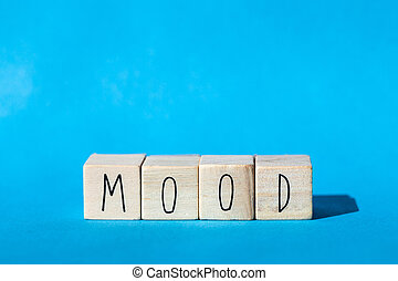 Wooden cubes with the word Mood with blue background, emotion concept