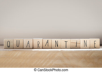 Wooden cubes with the word quarantine concept represented by wooden letter tiles, virus concept