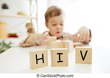 Wooden cubes with word HIV in hands of little boy at home.