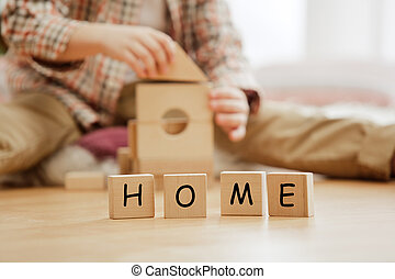 Wooden cubes with word HOME in hands of little boy