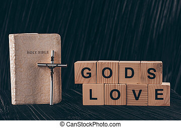 wooden cubes with words Gods Love and bible on black table