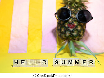 Wooden cubes with written words Hello summer and red lip pineapple wears sunglasses, having sun bath on bright yellow and pink pastel stripe background