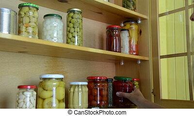 wooden cupboard jars - blonde girl puts jars of canned...