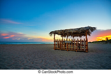 wooden curtain for massages on the beach at sunset