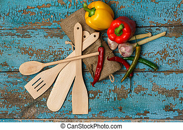 Wooden cutlery and different vegetables on shabby blue background