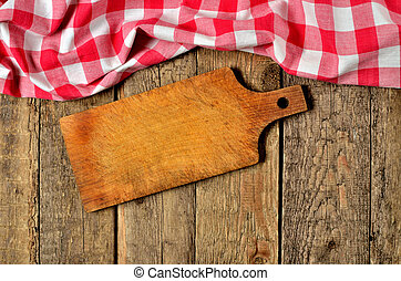 Wooden cutting board and a red checkered tablecloth top frame on wooden table background