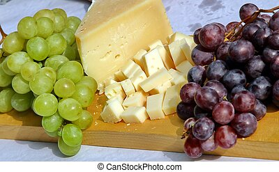 Wooden cutting board with Asiago cheese and black grapes and white grape