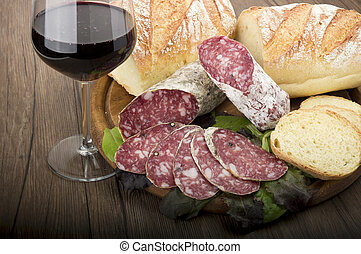 salami - wooden cutting board with salami and glass of Red...