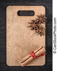 wooden cutting Board with star anise and cinnamon isolated on dark background