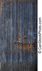Wooden dark blue, empty, old, peeled door for background. Rusty latch. Close up, banner, details.