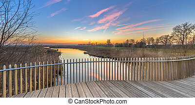 Wooden deck balustrade sunset over swamp