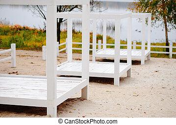 Wooden deck chairs on autumn beach