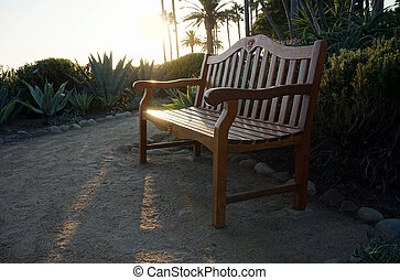 Wooden deck chairs on the beach at sunset.