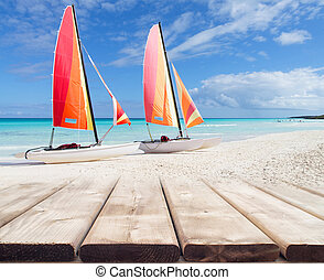 Wooden deck perspective with two colorful catamarans on white sandy beach blurred background, vacation concept