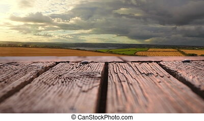 Wooden deck with a view of wide open fields - Low angle of a...