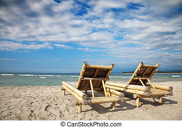 Wooden deckchairs on empty beach