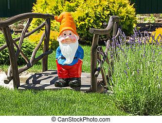 Wooden decorative bridge with garden dwarf  in home garden.