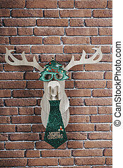 Wooden deer hanging on the wall decorated with glasses and christmas tie.
