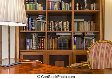Wooden desk and classic bookcase with books