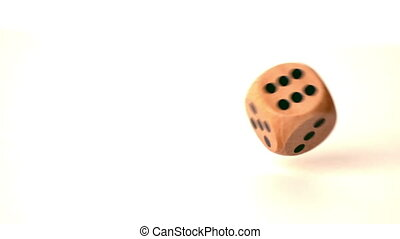 Wooden dice rolling on white surface - Wooden dice rolling...