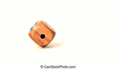 Wooden dice spinning on white surf
