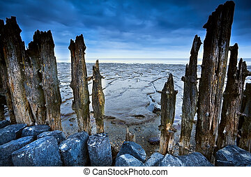 wooden dike and mud at low tide