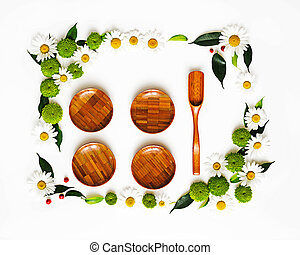 Wooden dishes with wreath frame from chamomile and chrysanthemum flowers, ficus leaves and ripe rowan on white background. Overhead view. Flat lay.