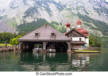 Wooden dock for boats with a temple and mountains in the background on Konigssee Lake, Austria