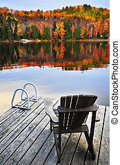 Wooden dock on autumn lake - Wooden dock with chair on calm ...