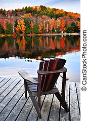 Wooden dock on autumn lake - Wooden dock with chair on calm...