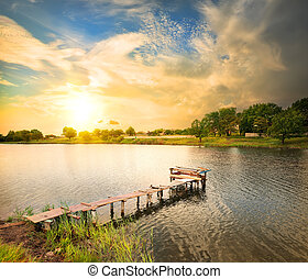 Wooden dock, pier, on a lake in the evening