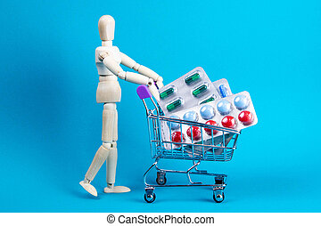 Wooden doll and metal shopping cart with pills on blue background. Various capsules, tablets and medicine on blue pastel trendy background. Pills concept