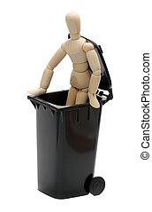 wooden doll in garbage bin