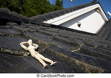 Wooden doll sleeping face up on a asian roof tiles from an...