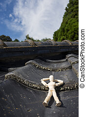 Wooden doll sleeping face up on a asian roof tiles in...