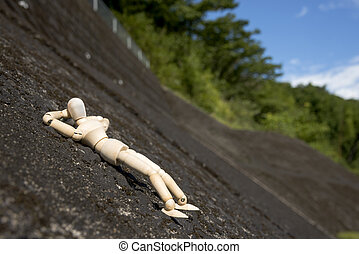 Wooden doll sleeping face up on a concrete slope in front of...