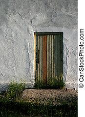 Wooden Door - A rough wooden door in a white wall that is...