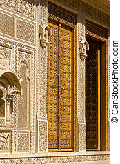 Wooden door and ornament on wall of palace in Jaisalmer...