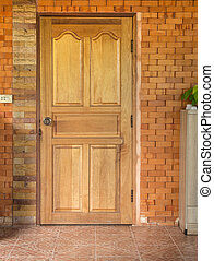 wooden door in brick wall background at home