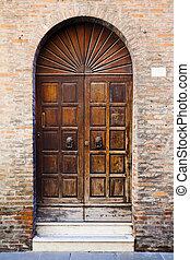 wooden door in brick wall of medieval house