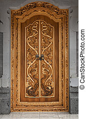 Wooden door of an old temple with carvings. Indonesia, Bali