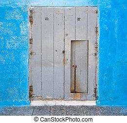 Wooden door on blue wall.