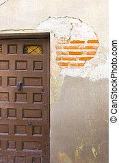 wooden door with chipped broken wall